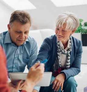 Mature Couple Meeting with Financial Advisor, selective focus to senior man and mature woman listening to financial advisor. She is pointing with index finger to digital tablet.